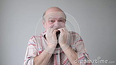 Hombre mayor mordiendo las uñas con expresión de preocupación almacen de video