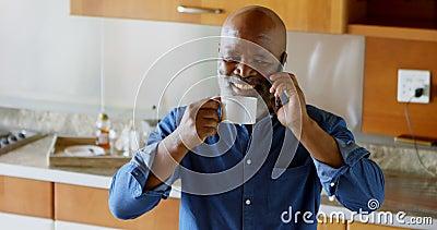 Hombre mayor que come café sólo mientras que habla en el teléfono móvil en la cocina 4k almacen de metraje de vídeo