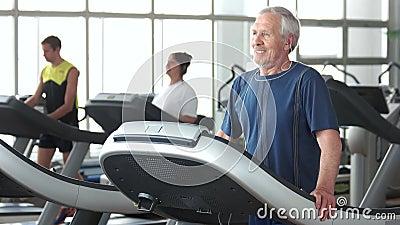 Hombre mayor que corre en la rueda de ardilla metrajes