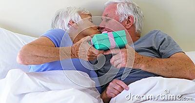 Hombre mayor que da el regalo de la sorpresa a la mujer en cama en dormitorio almacen de video