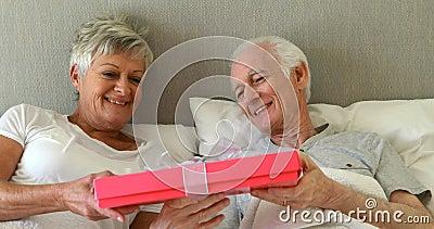 Hombre mayor que da un regalo de la sorpresa a la mujer en el dormitorio almacen de video