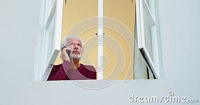 Hombre mayor que habla en el teléfono móvil por la ventana en casa 4k almacen de video