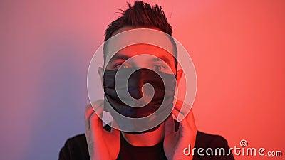 Hombre poniéndose una máscara de seguridad para prevenir el virus de la corona en la luz roja metrajes