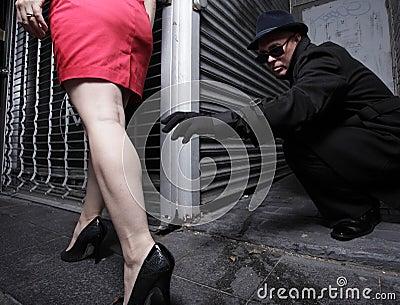 Hombre que alcanza para asir la pierna de los womans
