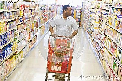 Hombre que empuja la carretilla a lo largo del pasillo del supermercado