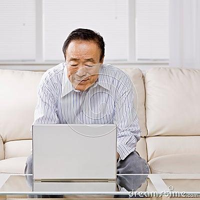 Hombre que pulsa en la computadora portátil