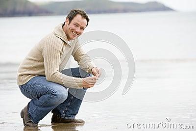 Hombre que se agacha en la playa