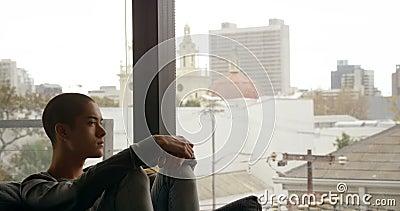 Hombre que se sienta en el sofá cerca de la ventana en casa 4k almacen de video