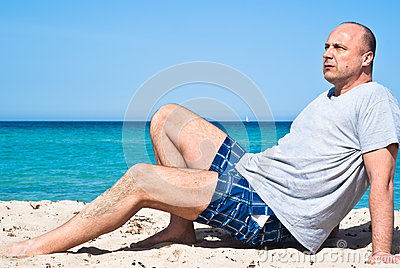 Hombre que se sienta en la playa para relajarse