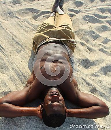 Hombre que toma el sol en la playa