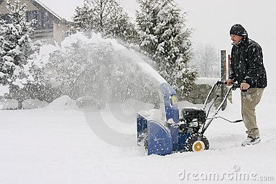 Hombre que usa un ventilador de nieve de gran alcance