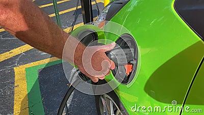 Hombre quitando un cable de carga de un vehículo eléctrico metrajes
