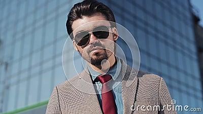 Hombre rico codicioso en las gafas de sol que llevan del traje elegante que cuentan el dinero y que miran a la cámara en el cierr almacen de metraje de vídeo