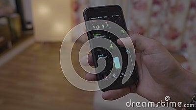 Hombre sano milenario que comprueba sus estadísticas de salud de la actividad juguetona usando el app en smartphone - almacen de video