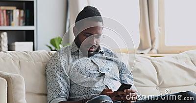 Hombre serio de África usando una aplicación para smartphones sentado en un sofá almacen de metraje de vídeo