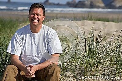 Hombre sonriente que se sienta en la playa