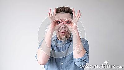 Hombre sosteniendo dedos cerca de los ojos como gafas Máscara como super héroe o búho metrajes