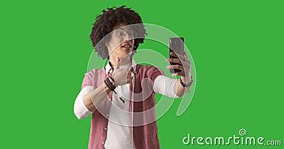 Hombre usando el teléfono móvil para la llamada video en fondo verde almacen de metraje de vídeo