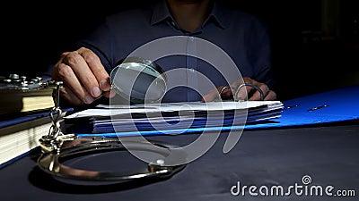 Hombre usando la lupa para los documentos de negocio del control para la investigación Evasión fiscal metrajes