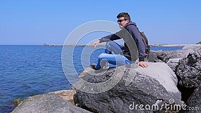 Hombre viajero viene a la orilla del mar se sienta enormes piedras admira el paisaje marino en las vacaciones almacen de metraje de vídeo