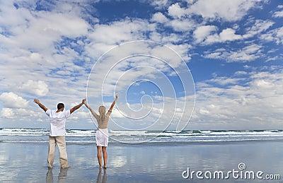 Hombre y mujer que celebran los brazos levantados en una playa