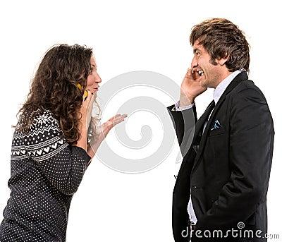 Hombre y mujer sonrientes con los teléfonos celulares