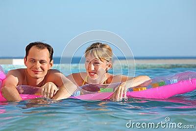 Hombre y mujeres que mienten en un colchón en piscina