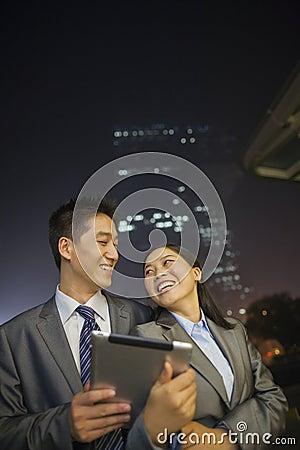 Hombres de negocios jovenes que sonríen y que sostienen la tableta digital, noche y al aire libre