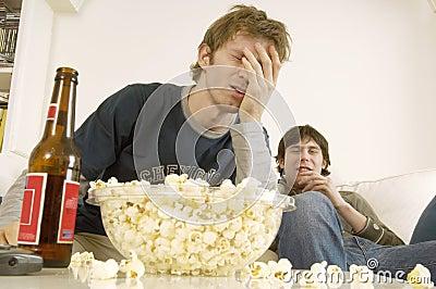 Hombres trastornados que ven la TV con palomitas y cerveza en la tabla