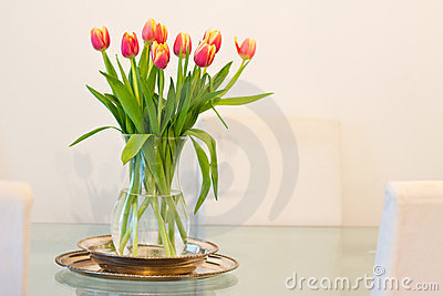 Home decoration: vase of tulips on glass table