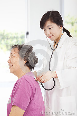 Home doctor measuring senior woman blood pressure