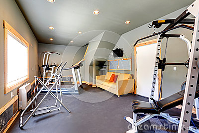 Home gym with yellow couch and TV