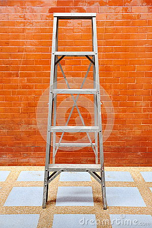 Home improvement concept with ladder and brick wall