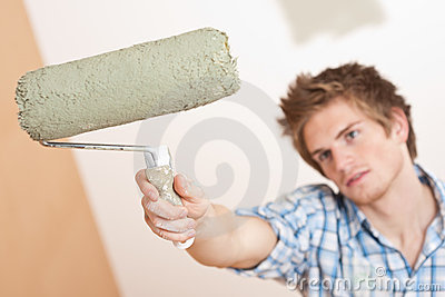 Home improvement: Young man holding paint roller