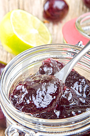 Home made cherry jam in a glass with a spoon