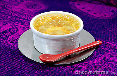 Home-made custard with a red ceramic spoon