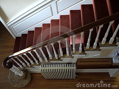 Home: sunlit staircase with red carpet