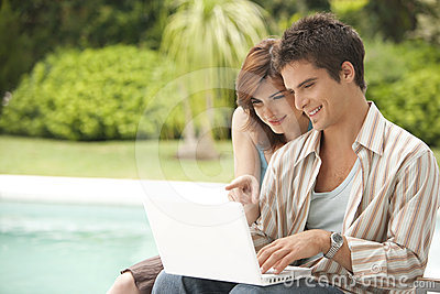 Home Tech Couple with Laptop by Pool