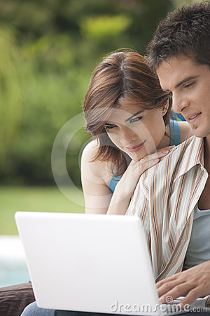 Home Tech Couple Looking at Laptop in Garden