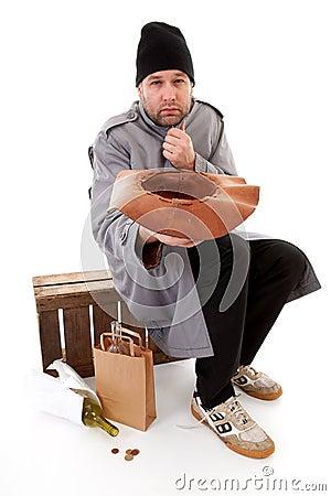 Homeless beggar holding hat for money