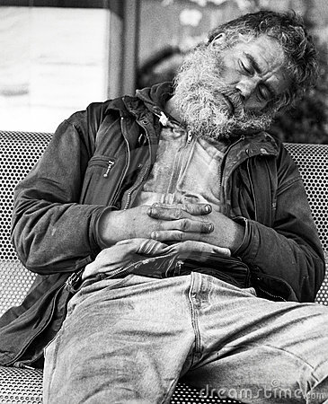 Homeless guy sleeping on a bench Editorial Stock Image