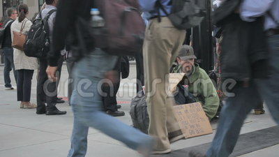 Homeless man. People walking past a homeless man