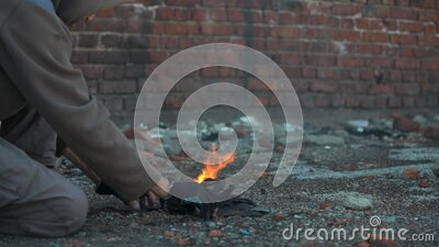 Homeless man warms his hands. Hands in black torn gloves Close up. Post-apocalypse scene.  stock video