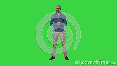 Homem árabe ocasional que fala à câmera que explica algo em uma tela verde, chave do croma video estoque