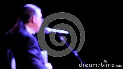 Homem abstrato de cabelos longos diante de um microfone em um fundo escuro Blurry Discurso de um empresário ou treinador de filme