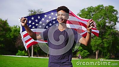 Homem afro-americano atrativo que guarda a bandeira americana em suas mãos no passeio traseiro no campo verde e no sorriso filme
