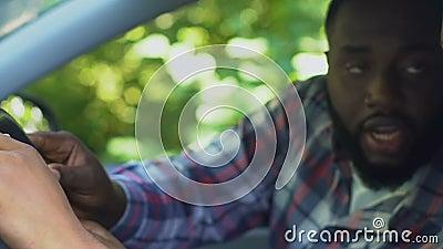 Homem afro-americano de meia-idade ensinando filho adolescente a dirigir carro, paternidade filme