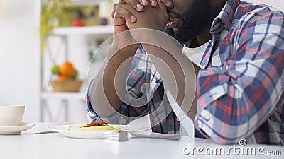 Homem afro-americano que reza antes de comer, pedindo que o deus abençoe o alimento, fé vídeos de arquivo