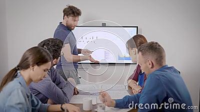 Homem apresenta relatório financeiro em reunião com colegas na sala de conferências, mostrando gráficos vídeos de arquivo