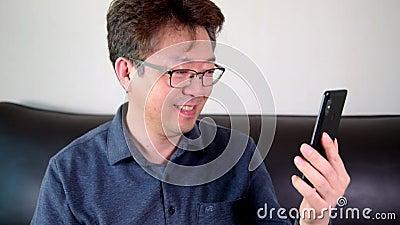 Homem asiático de meia-idade a ter uma vídeo-chamada feliz usando um smartphone filme